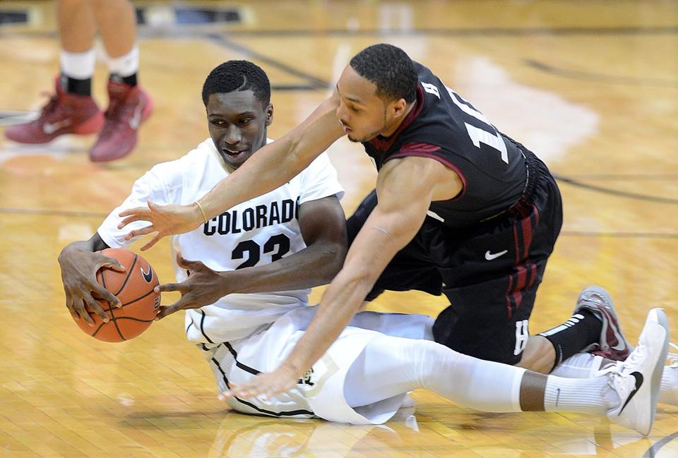 Harvard's Brandyn Curry takes a seat, but gets no respite from Colorado's Jaron Hopkins.